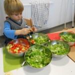 Kind sortiert Salat in verschiedene Schüsseln
